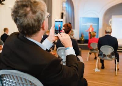 Ein Zuschauer fotografiert mit dem Handy die Rede von Bundesministerin Julia Klöckner